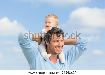 baby sitting on father