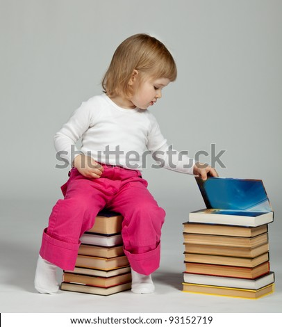 Baby sitting on stacked books; neutral background