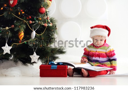 Baby sitting on the floor in a santa hat and reading a book. A child in a red cap. In the background, Christmas tree with ornaments. Christmas. The floor box with gifts.