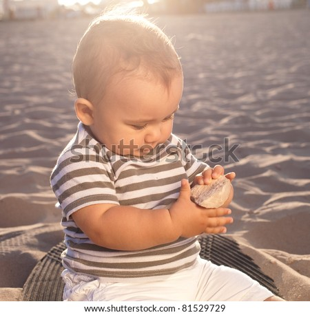 baby sitting on the sand watching a stone at sunset