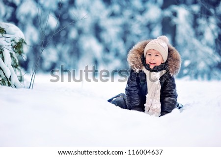 baby sitting on the snow in the woods