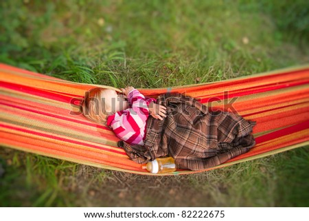 Baby sleep in hammock with bottle of juice