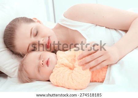 Baby sleep. Portrait of mother sleeping embracing her little child.