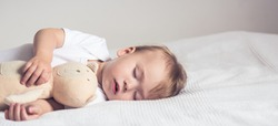Baby sleeping in crib. Peaceful baby lying on a bed while sleeping in a bright room with his teddy bear. Panoramic view.