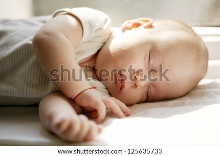 baby sleeping on white blanket on window