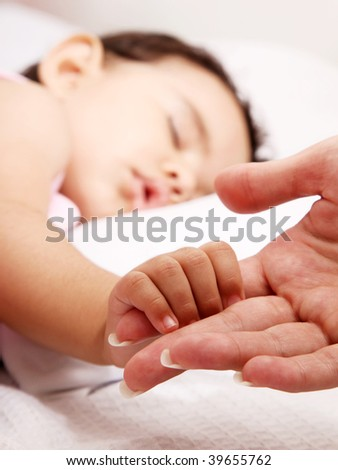 Baby sleeping take the hand of her mother