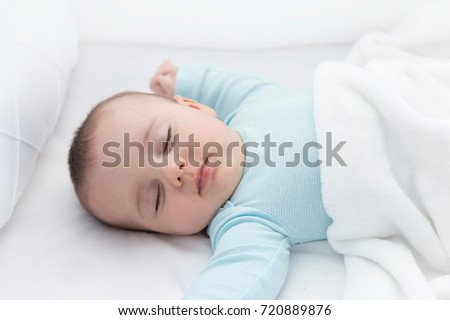 Baby sleeping with open arms and without pacifier in a cradle. Light blue pajama and white bed sheets.  Foto stock ©