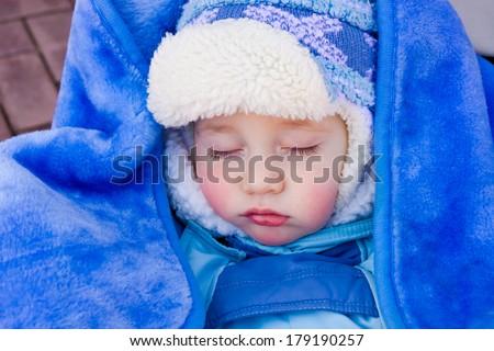 Baby sleeps in a stroller on a walk in the fresh air