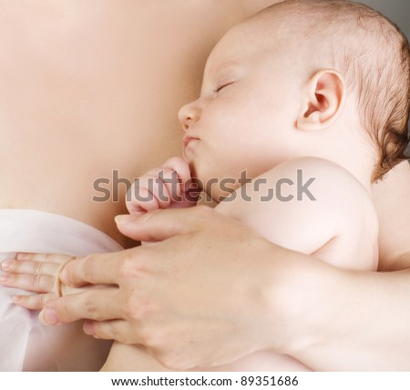 baby sleeps on mother's arms