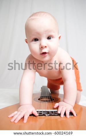Baby smiles  and plays a guitar