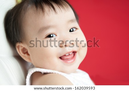 baby smiling and looking up to camera isolated on red background