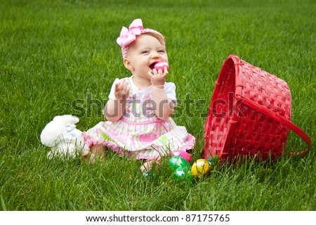 Baby Smiling while holding an Easter egg beside a red basket