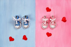 Baby sneakers on pink and blue background, baby shower concept