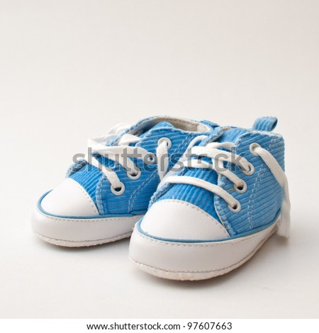 Baby sneakers. Pair of blue and white baby sneakers over gray background