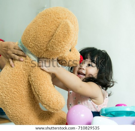 Baby so happy with big teddy bear doll soft toy , Happy sweet Asian girl hugging her big bear doll so tightly over white background, Little girl is very happy when she gets a big brown bear doll, Stock fotó ©