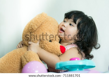 Baby so happy with big teddy bear doll soft toy, Happy sweet Asian girl hugging her big bear doll so tightly over white background, Little girl is very happy when she gets a big brown bear doll, Stock fotó ©