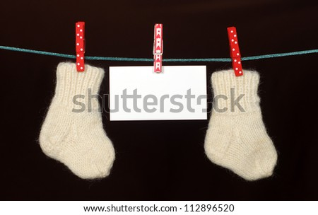 Baby sock and blank note hanging on the clothesline
