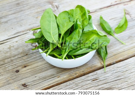 Baby spinach in a white bowl on a wooden board. Healthy food. Detox. Summer time