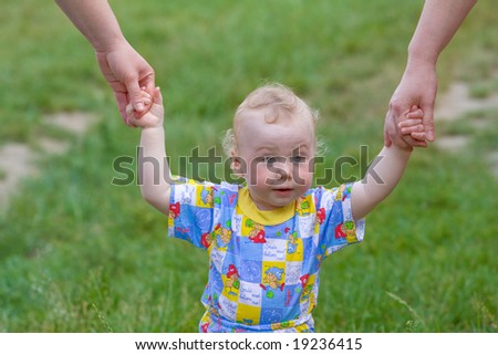 baby supported by mom and grandma - stock photo