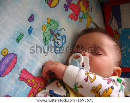 baby sweet dream on colourful blanket;  baby suck teat