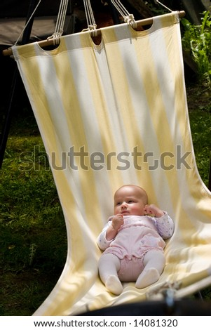 Baby  swinging in striped hammock on a summer day