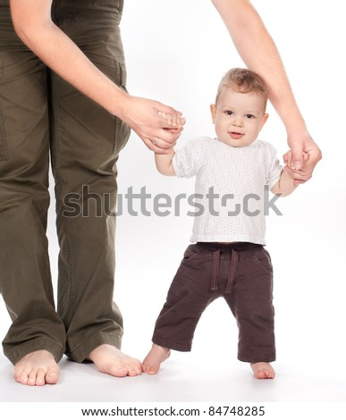 baby taking first steps with father help on white background