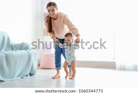 Baby taking first steps with mother's help at home