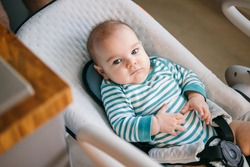 Baby three months old in the seat lounger and swing