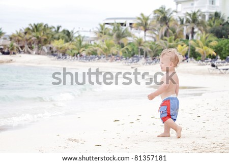 Baby, toddler boy having fun running on a tropical beach