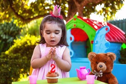Baby toddler girl in outdoor second birthday party clapping hands at cake with Teddy Bear as best friend, playhouse and tea set. Pink dress and crown.