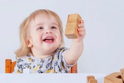 Baby toddler joyfully playing with wooden toys in children's room on a light background (concept of happy child, fun games)