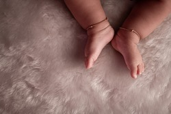 baby toes with anklet lying on a fur