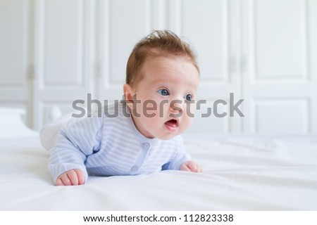 Baby tummy time, wearing blue clothes in a white nursery