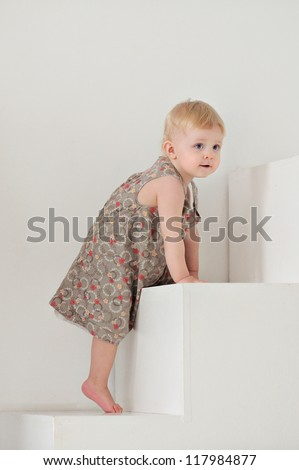 Baby up the white stairs. On a small child brown dress.