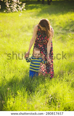 baby walking in green park holding hands of mother. happy little child playing outside with parents. first steps of infant. beautiful boy in spring blooming garden having fun with mom.