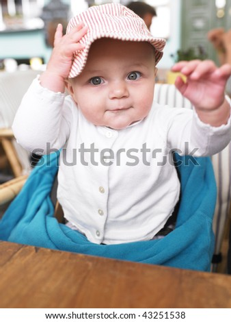 Baby wearing a hat sits in high chair at restaurant. Vertically framed shot.
