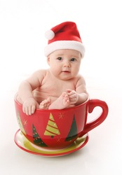 Baby wearing a santa hat sitting inside a giant Christmas tea cup.