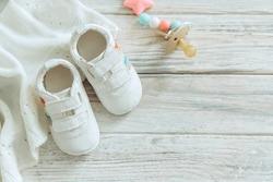 Baby white shoes and warm blanket on wooden background. Top view with copy space.