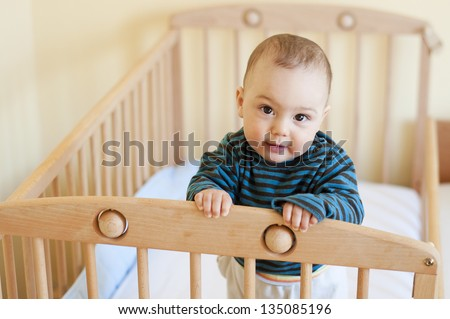 Baby with a cute happy face standing in a cot.