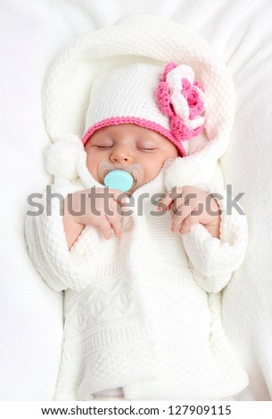 Baby with a knitted white hat baby on back