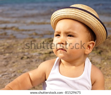 baby with a straw hat in the beach