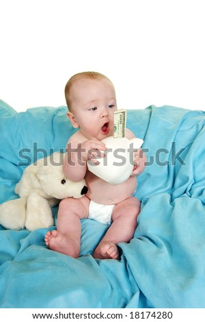 Baby with a surprised look at his piggy bank with a hundred dollor bill sticking out