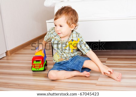 baby with a toy car on the floor at home