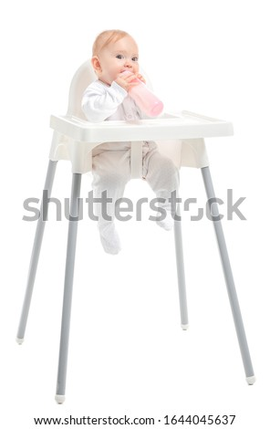 Baby with bottle of milk sitting in high-chair on white background Stock foto ©