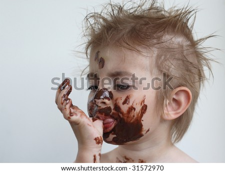 Baby with face covered in chocolate - stock photo