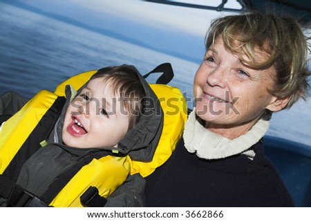 baby with grandmother on a boat doing faces
