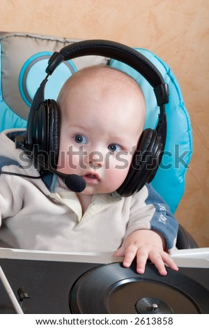 baby with headphones and microphone playing with turntable