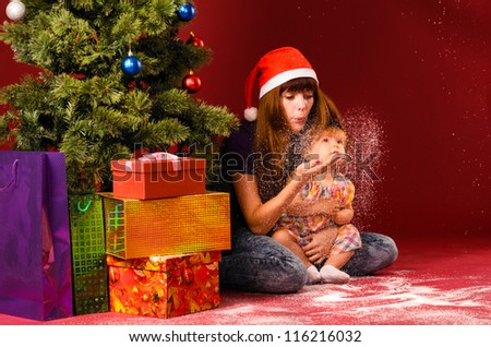 baby with her mother are blowing snow flakes near christmas tree