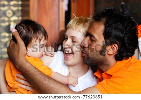 baby with mother and father in the room