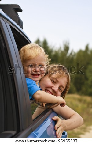 Baby with mother looking through car window